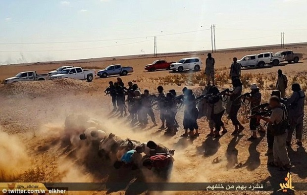 Barefooted with their hands bound behind their backs with rope, the prisoners are marched to the execution site in the desert near Deir ez Zor in Syria. ISIS fighters stand behind the line of men and the squad of jihadists begin to murder the prisoners