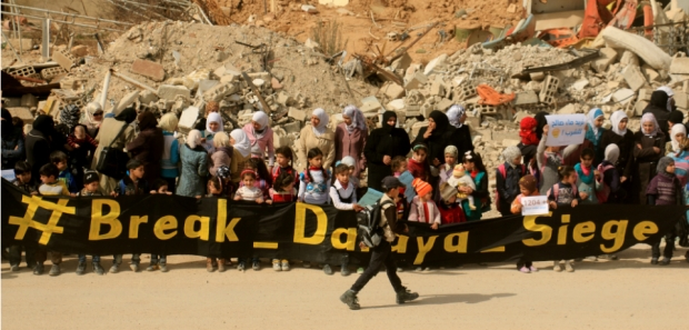 The photo shows a March 9, 2016 protest by local women and children in Daraya, who were calling on the government to allow for the delivery of food to the besieged city.
